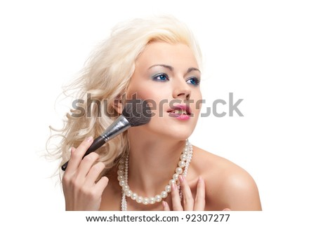 Portrait of beautiful young blonde woman with brush for make-up on a white background.