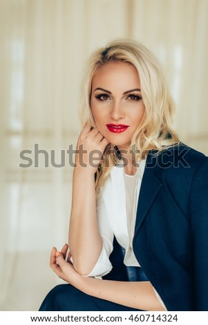 Portrait of beautiful young blonde woman with makeup in fashion clothes - stock photo