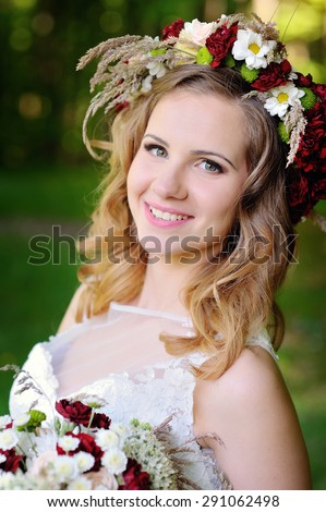 Portrait of beautiful young bride in park in spring - stock photo