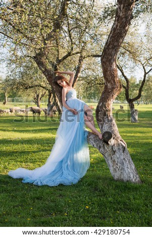 Portrait of beautiful young bride posing in the park or garden in blue dress outdoors on a bright sunny day green grass background