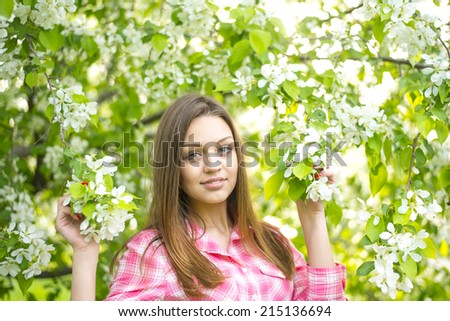 portrait of beautiful young brown hair woman standing near the apple tree on a warm summer sunny day Girl standing against sun light sky background Empty Copy space for inscription Looking at camera - stock photo