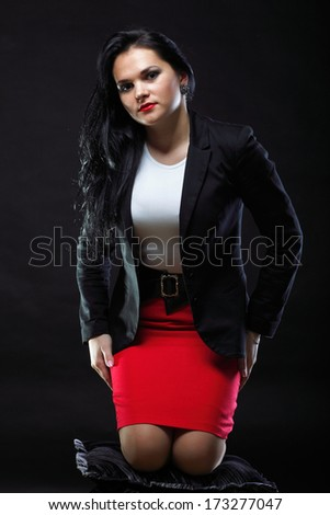 portrait of beautiful young brunette fashion girl red skirt on black background.