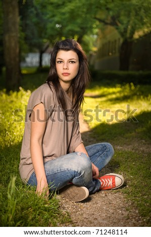 Portrait of beautiful young brunette sitting relaxed in the park.