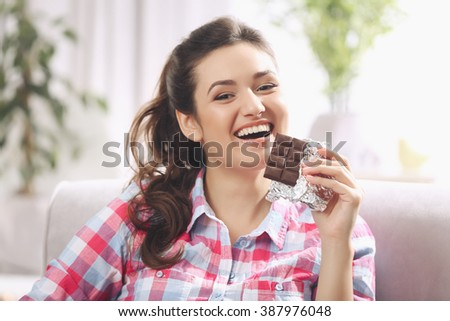 Portrait of beautiful young brunette with chocolate on sofa in the room , close up - stock photo