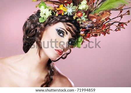 Portrait of beautiful young brunette with flowers in hair.