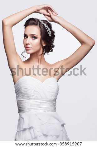 Portrait of beautiful young brunette woman bride in white Wedding Dress with hands up on light gray background