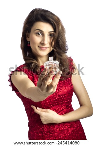 Portrait of beautiful young brunette woman giving you her favorite perfume with focus on the perfume