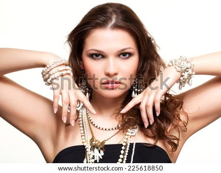 Portrait of beautiful young brunette woman in and earrings on white background - stock photo