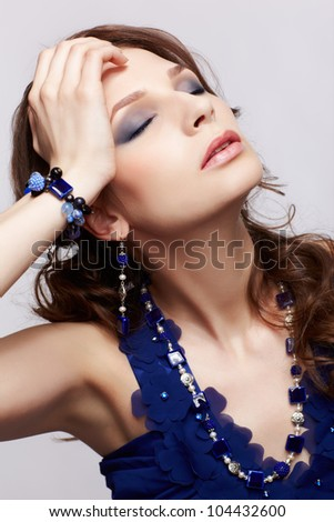 portrait of beautiful young brunette woman in blue dress, bracelet, ear-rings and beads touching her head and closing eyes