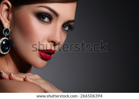 Portrait of beautiful young brunette woman in ear-rings - stock photo