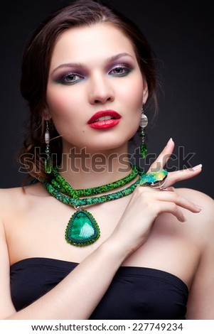 Portrait of beautiful young brunette woman in malachite necklace, pendent, ring and earrings on dark gray background