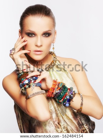 portrait of beautiful young brunette woman in multiple bracelets and other jewellery on gray