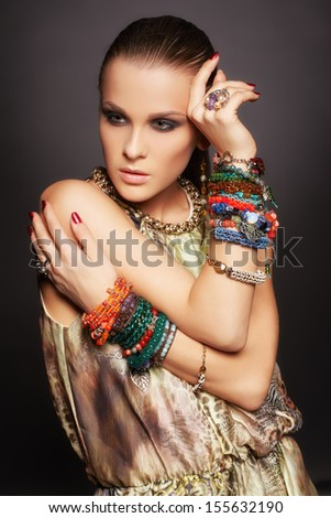 portrait of beautiful young brunette woman in numerous bracelets on dark gray