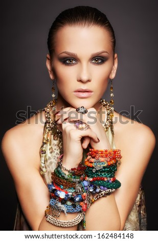 portrait of beautiful young brunette woman in rings and multiple bracelets on dark gray