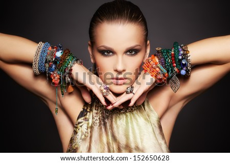 portrait of beautiful young brunette woman posing in rings and multiple bracelets on dark gray - stock photo