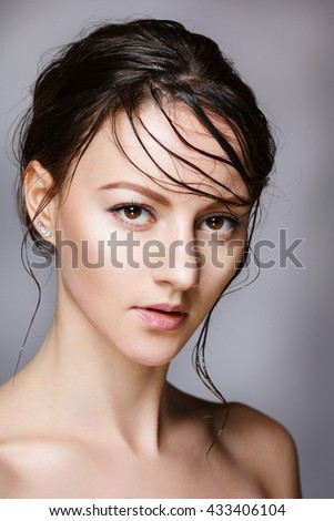 Portrait of beautiful young brunette woman with clean face on white background