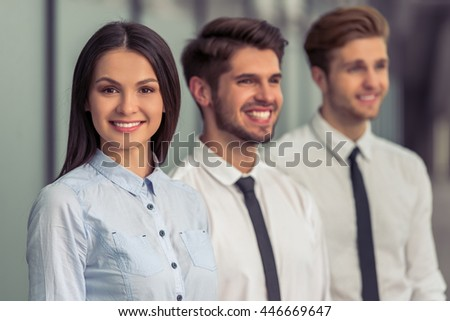 Portrait of beautiful young business lady in classic clothes looking at camera and smiling. Her colleagues are standing near