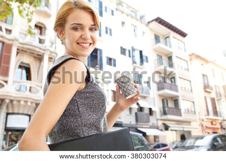 Portrait of beautiful young business woman commuter walking in classic office city, holding coffee cup, smiling and looking. Professional businesswoman drinking coffee on the go, lifestyle exterior. - stock photo