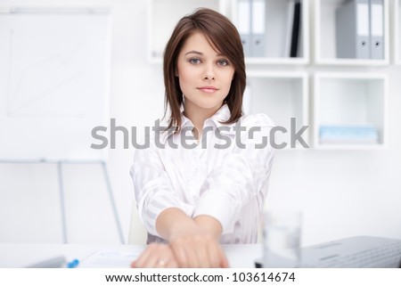Portrait of beautiful young business woman sitting at desk at office - stock photo