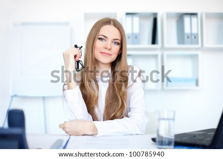 Portrait of beautiful young business woman sitting at desk in bright office - stock photo