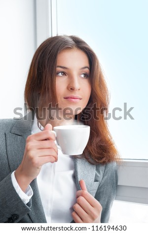 Portrait of beautiful young business woman wearing formal clothes drinking coffee while resting at her office near big window - stock photo