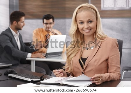 Portrait of beautiful young businesswoman sitting at desk in office, working, smiling, looking at camera. - stock photo