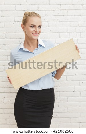 portrait of beautiful young businesswoman smiling while holding blank board - stock photo
