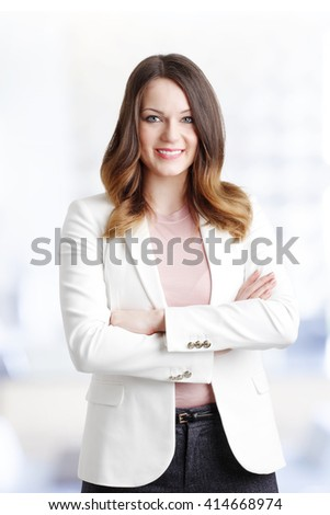 Portrait of beautiful young businesswoman standing at office while looking at camera and smiling. - stock photo