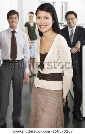 Portrait of beautiful young businesswoman with colleagues in background