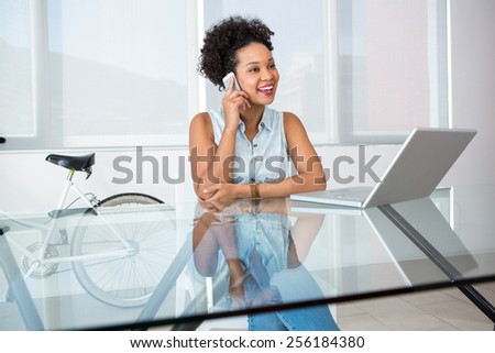 Portrait of beautiful young casual woman using cellphone in office