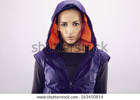 Portrait of beautiful young caucasian woman in a hooded jacket on grey background. Fitness woman in sportswear looking at camera - stock photo