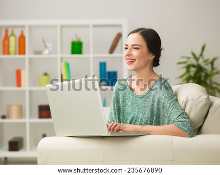 portrait of beautiful young caucasian woman siting on sofa at home, using lapop and laughing
