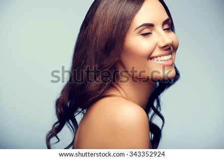 portrait of beautiful young cheerful smiling woman with naked shoulders