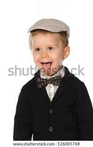 Portrait of beautiful young child with hat and bow tie and his tongue out