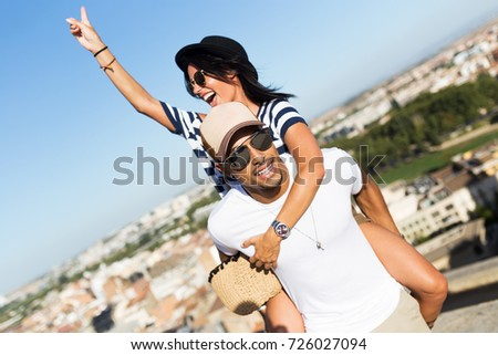 Portrait of beautiful young couple enjoying summer on the street.