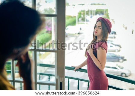 Portrait of beautiful young couple having conversation while looking at each other over a window background outdoors - stock photo