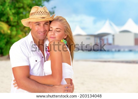 Portrait of beautiful young couple hugging outdoors, spending romantic honeymoon vacation on luxury beach resort, summer time concept - stock photo