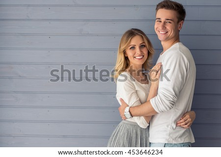 Portrait of beautiful young couple in casual clothes hugging, looking at camera and smiling, standing against gray wall
