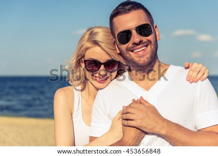 Portrait of beautiful young couple in sun glasses hugging, looking at camera and smiling, sunny seaside in the background - stock photo