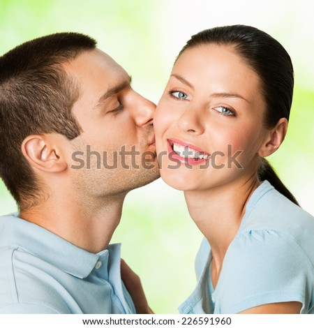 Portrait of beautiful young couple kissing, outdoor - stock photo