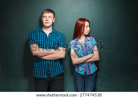 Portrait Of Beautiful Young Couple Over Dark Green Wall. Hard times in relationships. Red-haired woman and blonde man in check shirts. - stock photo
