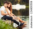 Portrait of beautiful young couple sitting on the board of lake - stock photo