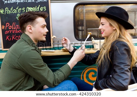 Portrait of beautiful young couple visiting eat market in the street.