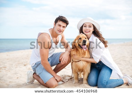 Portrait of beautiful young couple with their dog on the beach - stock photo