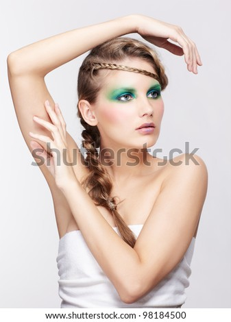portrait of beautiful young dark blonde woman with creative braid coiffure posing on gray