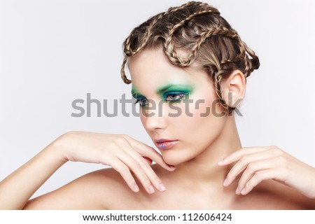 portrait of beautiful young dark blonde woman with creative braid hairdo and green eye shades touching her chin