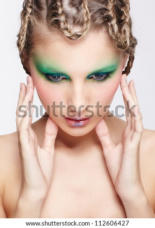 portrait of beautiful young dark blonde woman with creative braid hairdo and green eye shades touching her face