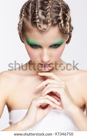 portrait of beautiful young dark blonde woman with creative braid hairdo and green eye shades