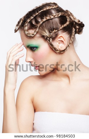 portrait of beautiful young dark blonde woman with creative braid hairdo and green eye shades touching her forehead