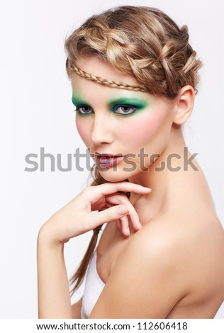 portrait of beautiful young dark blonde woman with creative braid hairdo and green eye shades make up on gray - stock photo